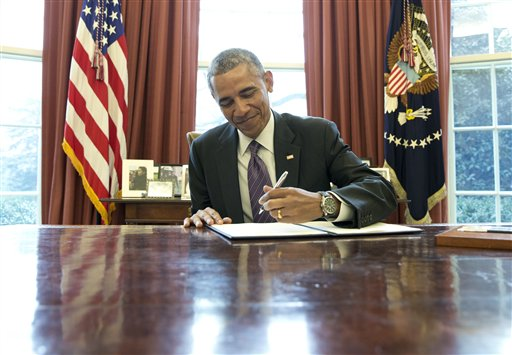 President Barack Obama signs a presidential memorandum on paid leave, Thursday, Jan. 15, 2015, in the Oval Office of the White House in Washington. The presidential memorandum is to direct federal agencies to advance six weeks of paid sick leave that federal workers could use as paid family leave. Workers would have to pay back the sick leave over time. (AP Photo/Carolyn Kaster)