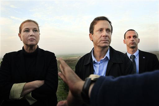 In this Thursday, Dec. 11, 2014 file photo, Israeli politicians Isaac Herzog, right, and Tzipi Livni listen during a tour along the Israel and Gaza Strip border. When Prime Minister Benjamin Netanyahu dissolved his unwieldy coalition and called new elections last month, he appeared to be a lock to return to office. But a new center-left alliance has suddenly surged in the polls past his ruling Likud party to become the largest parliamentary faction and turned the March 17 vote into a toss-up. (AP Photo/Tsafrir Abayov, File )