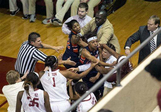 A fight between Auburn guard Hasina Muhammad (00) and Alabama guard Breanna Hayden (5) spills into the Alabama bench during an NCAA college basketball game  Thursday, Jan. 22, 2015, at Foster Auditorium in Tuscaloosa, Ala. (AP Photo/AL.com, Vasha Hunt)