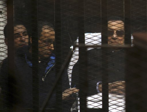 In this Nov. 29, 2014 file photo, ousted Egyptian President Hosni Mubarak, 86, lies on a gurney, next to his son Gamal, second left, in the defendants cage, during a court hearing in Cairo, Egypt. Egypt's top appeals court has ordered the retrial of the deposed president and his two sons in a corruption case, a move that could pave the way for the former autocrat's release. The Appeals Court announced its ruling in a brief session Tuesday, Jan. 13, 2015, carried live on several Egyptian TV networks. (AP Photo/Tarek el-Gabbas, File)