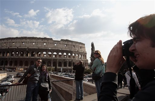 In this Tuesday, March 22, 2011 file photo, tourists take pictures in front of Rome's ancient Colosseum. A strong U.S. dollar is making world travel cheaper for Americans in 2015. (AP Photo/Gregorio Borgia, File)
