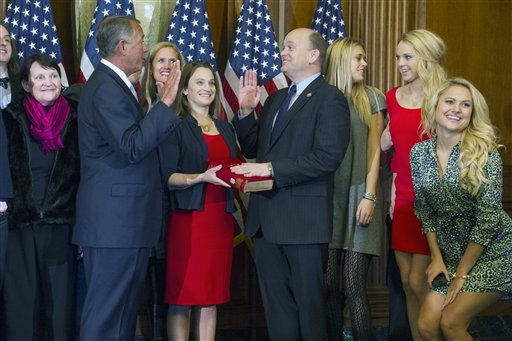 House Speaker John Boehner of Ohio administers a ceremonial re-enactment of the oath-of-office to Rep. Tom Reed, D-N.Y., accompanied by his wife Jean Reed and other family members, Tuesday, Jan. 6, 2015, on Capitol Hill in Washington. (AP Photo/Cliff Owen)