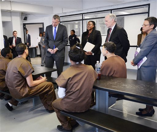 In this Dec. 17, 2014 file photo, New York City Mayor Bill de Blasio, center left, meets with youth offenders as Acting Deputy Commissioner of Youthful Offenders, Adult Programming and Community Partnerships Winette Saunders-Halyard, center, and  Department Correction Commissioner Joe Ponte, right, look on, at Second Chance Housing which serves as alternative housing for incarcerated adolescents on Rikers Island in New York. In the midst of heightened scrutiny to reform New York City's jails, reports of violence by guards against inmates reached an all-time high in 2014, according to documents obtained by The Associated Press. De Blasio had come to the jail to announce the city had ended its longstanding practice of sending 16- and 17-year-old inmates to solitary confinement for breaking rules.  (AP Photo/The Daily News, Susan Watts, Pool, File)
