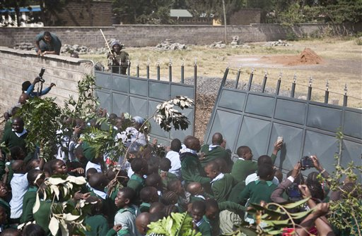 Kenyan school pupils and activists push down the wall leading to their playground, during a protest against the removal of their school's playground, at the Langata Road Primary School, in Nairobi, Kenya Monday, Jan. 19, 2015. Kenyan police tear-gassed schoolchildren demonstrating against the removal of their school's playground, the land of which has been allegedly grabbed by a powerful politician, according to a Kenyan human rights activist. (AP Photo/Brian Inganga)