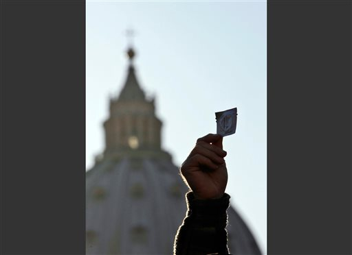 "In this March 23, 2009 file photo, St. Peter's Basilica is seen behind a hand of a demonstrator holding a condom, on the edge of the Vatican's St. Peter's Square, in Rome. During his return from The Philippines, Monday, Jan. 19, 2015, Pope Francis showed his more conservative side by upholding church teachings on contraception, and saying that Catholics don't have to breed ""like rabbits"" and should instead practice responsible parenting. (AP Photo/Alessandra Tarantino, File)"