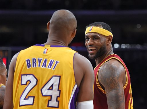 Cleveland Cavaliers forward LeBron James, right, smiles at Los Angeles Lakers guard Kobe Bryant after missing a dunk during the first half of an NBA basketball game, Thursday, Jan. 15, 2015, in Los Angeles. (AP Photo/Mark J. Terrill)