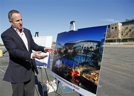 Chris Meany, senior vice president of Hollywood Park Land Company unveils an architectural rendering of a proposed NFL stadium at Hollywood Park in Inglewood, Calif., Monday, Jan. 5, 2015.  The owner of the St. Louis Rams plans to build an NFL stadium in Los Angeles County, boosting the chances that pro football could return to the region, according to the Los Angeles Times. Stan Kroenke has partnered with Stockbridge Capital Group, owners of the 238-acre Hollywood Park site in Inglewood, the newspaper reported Monday. (AP Photo/Nick Ut)
