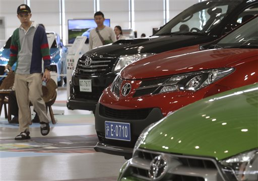 In this May 8, 2014 photo, visitors look at cars displayed at a Toyota gallery in Tokyo. Toyota Motor Corp. stayed at the top in global vehicle sales in 2014, but is pessimistic about this year. The Japanese automaker sold 10.23 million vehicles, beating out Volkswagen and General Motors to take that auto industry crown for the third year straight. Toyota was less upbeat about the future, expecting to sell fewer trucks and cars this year, at 10.15 million vehicles, down 1 percent year-on-year, according to numbers released Wednesday, Jan. 21, 2015. (AP Photo/Koji Sasahara, File)