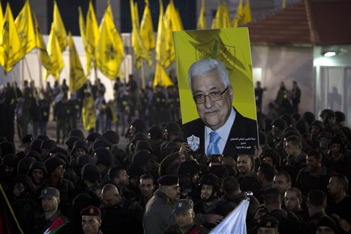 Palestinians hold up a poster showing President Mahmoud Abbas, as they celebrate the 50th anniversary of the Fatah movement in the West Bank city of Ramallah, Wednesday, Dec. 31, 2014. Palestinian President Mahmoud Abbas said the Palestinians will join the International Criminal Court, a move that sets the stage for filing a war crimes case against Israel. Abbas made the announcement in the West Bank on Wednesday, a day after the U.N. Security Council failed to pass a resolution that had aimed to set a deadline for Israel to end its occupation of territories sought by the Palestinians. (AP Photo/Majdi Mohammed)