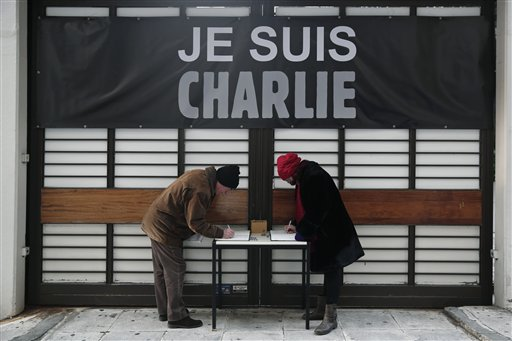 """People write messages under the slogan """"I am Charlie,"""" outside the French Institute in Athens on Thursday, Jan. 8, 2015. Several hundred people took part in the gathering, as France held a day of mourning for 12 people slain at the Charlie Hebdo offices. Similar protests were planned in several countries worldwide. (AP Photo/Petros Giannakouris)"""