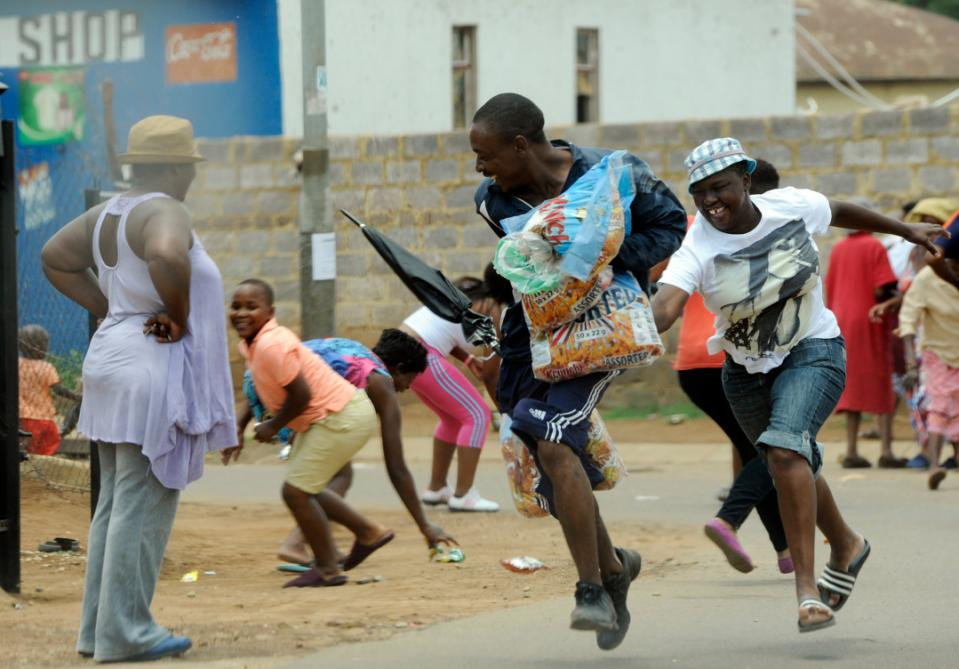 Looters make off with goods from a store in Soweto, South Africa, Thursday, Jan 22, 2015. About 70 people in South Africa have been arrested because of violent protests and looting, much of which was aimed at shops owned by nationals from other African countries, local media reported Thursday. (AP Photo)