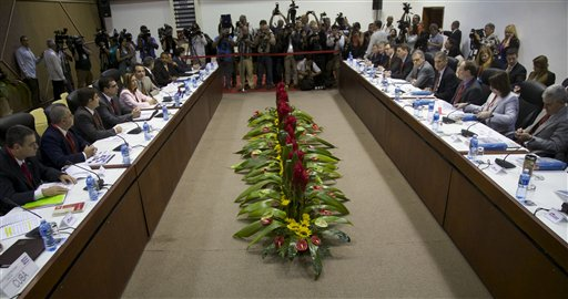 Members of a U.S. delegation, right, and Cuban delegates, left, sit across from each other as they begin negotiations, in Havana, Cuba, Wednesday, Jan. 21, 2015. The highest-level U.S. delegation to Cuba in decades kicked off two days of negotiations Wednesday after grand promises by President Barack Obama about change on the island and a somber warning from Cuba to abandon hopes of reforming the communist government. (AP Photo/Desmond Boylan)