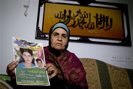 In this Tuesday, Jan. 27, 2015 photo, Palestinian Khawla Al-Khatib, holds a poster of her 14-year-old daughter Malak al-Khatib, detained in Israel, in the village of Beitin near the West Bank city of Ramallah. The Palestinian suspect, charged with stone throwing and possession of a knife, entered the courtroom and was sentenced to two months in prison. The scene has played out like many others in Israeli military courts. Except this time, the suspect was a 14-year-old girl. Malak al-Khatib was arrested last month near her sleepy village in the West Bank. Hers is a rare case of a female Palestinian minor held by Israel that has gripped Palestinians, who say her treatment demonstrates Israel's excessive measures against stone-throwing youth. (AP Photo/Majdi Mohammed)