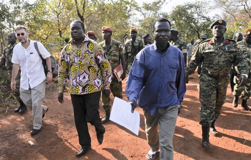 In this photo taken Friday, Jan. 16, 2015 and released by the Uganda People's Defence Force (UPDF), a man said by the UPDF to be the wanted Lord's Resistance Army (LRA) commander Dominic Ongwen, center-right, is handed over by the UPDF to the African Union Regional Task Force who later handed him over to Central African Republic authorities, in the Central African Republic. Central African Republic's Seleka rebels, who once overthrew the government, say they're entitled to a $5 million reward from the U.S. government because they say they captured and handed over the wanted international war crimes suspect Dominic Ongwen to American forces. (AP Photo/Uganda People's Defence Force, Mugisha Richard)