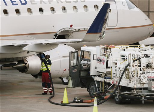 In this Jan. 15, 2015 photo, a worker prepares to fuel a United Express aircraft after it arrived at Dallas-Fort Worth International Airport, in Grapevine, Texas. Airlines will save billions this year thanks to cheaper jet fuel, but they aren't likely to share the bounty with passengers _ not while so many flights are already full. (AP Photo/Tony Gutierrez)