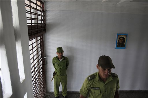 "In this April 9, 2013 file photo, military guards stand in a room decorated with an image of revolutionary hero Ernesto ""Che"" Guevara outside prison cells at the Combinado del Este prison during a media tour in Havana, Cuba. Three Cuban political prisoners were freed Wednesday, Jan. 7, 2015 and a leading human rights advocate said he believed their liberation was part of a U.S.-Cuban deal to release 53 dissidents. The three freed prisoners are Enrique Figuerola Miranda, Diango Vargas Martin and his twin brother Bianko Vargas Martin, according to Cuba's Human Rights and Reconciliation Commission. (AP Photo/Franklin Reyes, File)"