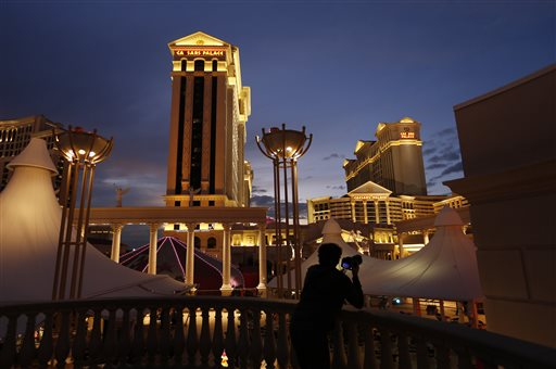 In this Monday, Jan. 12, 2015 photo, a man takes pictures of Caesars Palace hotel and casino, in Las Vegas. The company said Friday, Jan. 9, it has a majority of the holders of its debt on board with a pre-planned bankruptcy agreement that would reorganize Caesars Entertainment Operating Corp. into two separate companies, one to own casino-hotels and the other to lease them, and cut its existing debt by about $10 billion. (AP Photo/John Locher)