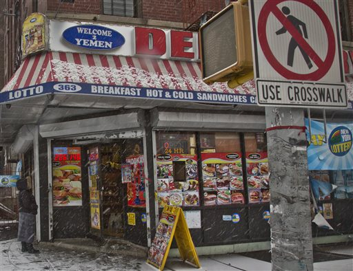 A woman approaches a deli, Tuesday, Jan. 6, 2015, where a robbery occurred the night before, in the Bronx borough of New York. A manhunt was underway Tuesday for at least two suspects who shot and wounded two New York City plainclothes police officers responding to the robbery late Monday. (AP Photo/Bebeto Matthews)