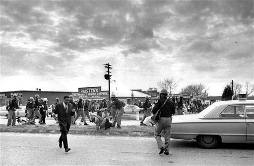 "In this March 7, 1965 file photo, John Lewis, center, of the Student Nonviolent Coordinating Committee, is forced to the ground by a trooper as state troopers break up the demonstration on what has become known as ""Bloody Sunday"" in Selma, Ala. Supporters of black voting rights organized a march from Selma to Montgomery to protest the killing of a demonstrator by a state trooper and to improve voter registration for blacks, who are discouraged to register.  (AP Photo)"