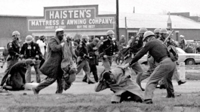 "Alabama state troopers swing nightsticks to break up the ""Bloody Sunday"" voting march in Selma, Ala., on March 7, 1965. John Lewis, front right, of the Student Non-violent Coordinating Committee, is put on the ground by a trooper. (Associated Press)"
