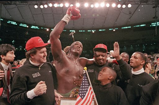 """In this Feb. 11, 1990, file photo, heavyweight boxer James """"Buster"""" Douglas waves his gloved hand to the cheering crowd as he makes his way to the dressing room following a 10th round knockout victory over Mike Tyson in a scheduled 12-round championship bout at the Tokyo Dome. Others are unidentified. It's been 25 years since one of the most stunning upsets in sports history. (AP Photo/Sadayuki Mikami, File)"""