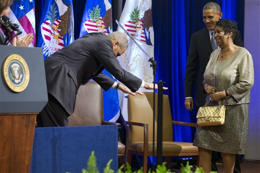 President Barack Obama, right, smiles as outgoing Attorney General Eric Holder, left, bows to singer Aretha Franklin as she arrives in a surprise appearance to sing at an event celebrating Holder at the Department of Justice in Washington, Friday, Feb. 27, 2015. (AP Photo/Jacquelyn Martin)