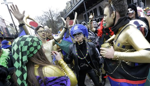 Revelers dance to a brass band in the French Quarter on Mardi Gras in New Orleans, Tuesday, Feb. 17, 2015. Revelers in glitzy costumes filled the streets of New Orleans for the annual fat Tuesday bash, opening a day of partying, parades and good-natured jostling for beads and trinkets tossed from passing floats. (AP Photo/Gerald Herbert)
