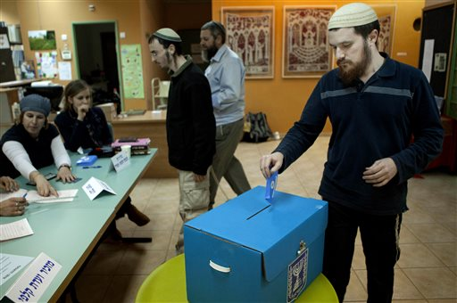 In this Jan. 22, 2013, file photo, an Israeli Jewish settler votes in the settlement of Elon Moreh in the West Bank, during legislative elections. With few exceptions, Israel does not allow absentee voting. But when the country goes to the polls next month, hundreds of thousands of West Bank settlers will be casting votes, even though they do not reside in sovereign Israeli territory. (AP Photo/Dan Balilty, File)