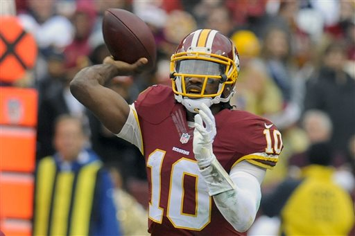 In this Sunday, Dec. 28, 2014 file photo, Washington Redskins quarterback Robert Griffin III (10) passes the ball during the first half of an NFL football game against the Dallas Cowboys in Landover, Md. Former Redskins head coach Mike Shanahan says things went downhill for him in Washington because Robert Griffin III and team owner Dan Snyder both wanted the quarterback to become a dropback passer, Wednesday, Feb. 18, 2015. (AP Photo/Richard Lipski, File)