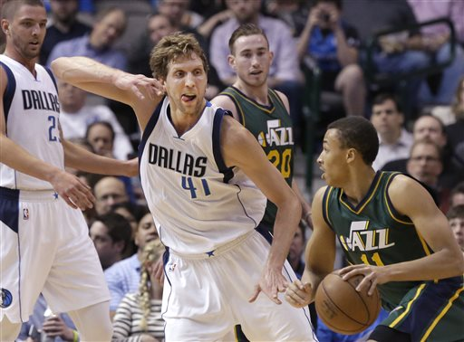 Dallas Mavericks forward Dirk Nowitzki (41) defends against Utah Jazz guard Dante Exum (11) as Mavericks Chandler Parsons (25) and Jazz Gordon Hayward (20) look on during the first half of an NBA basketball game Wednesday, Feb. 11, 2015, in Dallas. (AP Photo/LM Otero)