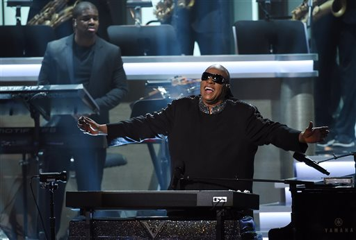 """Stevie Wonder takes in applause from the stage during the finale of """"Stevie Wonder: Songs in the Key of Life - An All-Star Grammy Salute,"""" at the Nokia Theatre L.A. Live on Tuesday, Feb. 10, 2015, in Los Angeles. (Photo by Chris Pizzello/Invision/AP)"""