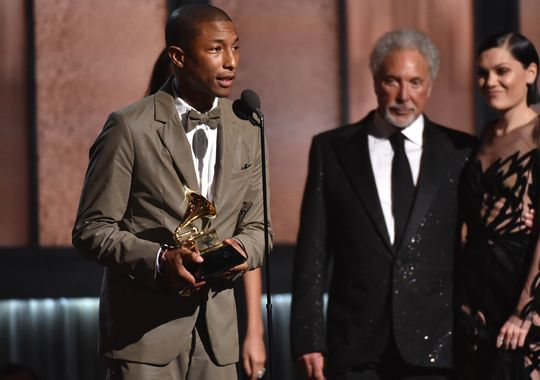 "Pharrell Williams accepts the award for best pop solo performance for ""Happy"" at the Grammys. (John Shearer/Invision/AP)"