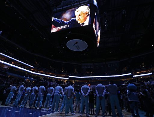 "Charlotte Hornets players pause with the Indiana Pacers and the crowd for a moment of silence in honor of former North Carolina head coach Dean Smith before an NBA basketball game in Charlotte, N.C., Sunday, Feb. 8, 2015. Smith, the North Carolina basketball coaching great who won two national championships, died ""peacefully"" at his home Saturday night, Feb. 7, 2015, the school said in a statement Sunday from Smith's family. He was 83. (AP Photo/Chuck Burton)"