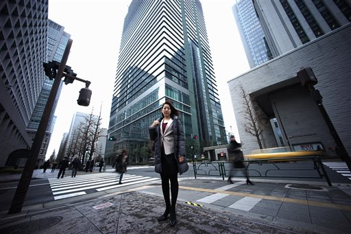 In this Jan. 21, 2015 photo, Eriko Sekiguchi, 36, stands at a crossroad in Tokyo. Often toiling 14 hours a day for a major trading company, including early morning meetings and after-hours, Sekiguchi used just eight of her 20 paid vacation days last year. Six of those days were for being sick. (AP Photo/Eugene Hoshiko)