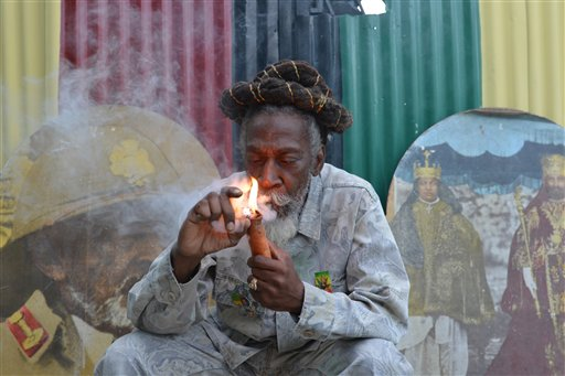 """In this Aug. 28, 2014 file photo, legalization advocate and reggae legend Bunny Wailer smokes a pipe stuffed with marijuana during a """"reasoning"""" session in a yard in Kingston, Jamaica. Jamaica lawmakers on Tuesday, Feb. 24, 2015, passed an act to decriminalize small amounts of pot and establish a licensing agency to regulate a lawful medical marijuana industry on the island. (AP Photo/David McFadden, File)"""