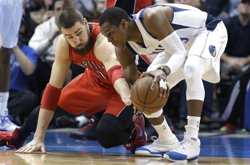 Toronto Raptors center Jonas Valanciunas, left, reaches for the ball against Dallas Mavericks guard Rajon Rondo (9) during the first half of an NBA basketball game Tuesday, Feb. 24, 2015, in Dallas. (AP Photo/LM Otero)