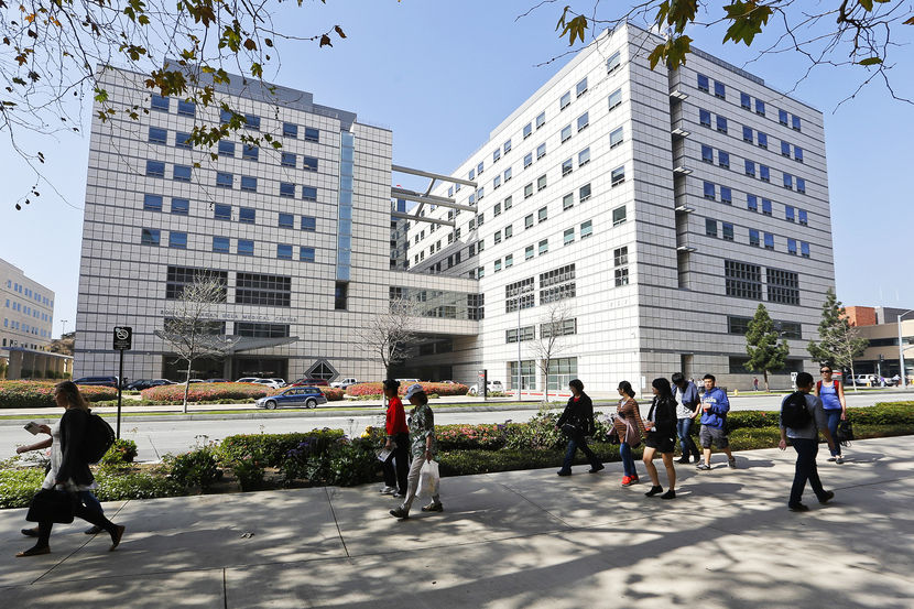 "People walk near the Ronald Reagan UCLA Medical Center in Los Angeles building in Los Angeles, Thursday, Feb. 19, 2015. A ""superbug"" outbreak suspected in the deaths of two patients at UCLA Medical Center in Los Angeles has raised questions about the adequacy of the procedures for disinfecting a medical instrument used on more than a half-million people in the U.S. every year. (AP Photo/Damian Dovarganes)"