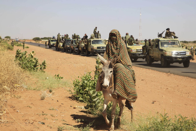 In this Thursday, Nov. 20, 2014 photo taken on a government organized media tour, a woman rides a donkey past a convoy of government troops in Tabit village in the North Darfur region of Sudan, where allegations surfaced of rape of women by government allied troops. The spokesman for the joint United Nations African Union peacekeeping force in Darfur says the Sudan government has asked his mission to prepare plans to exit the country. This comes amid tension between the mission and the government over an investigation into allegations of mass rape in the violence-torn western region of Darfur. (AP Photo/Abd Raouf)