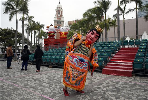 """A performer from Taiwan dressed as the """"Third Prince"""" poses for a photograph in front of the sheep decorations during the rehearsal of International Chinese New Year Night Parade in Hong Kong Wednesday, Feb. 18, 2015. Decades ago the Chinese New Year holiday, also known as Spring Festival, had little impact outside of China. But as the country has gained outsized economic influence, the holiday, which has enormous cultural significance in the Chinese-speaking world, has become more prominent. (AP Photo/Kin Cheung)"""