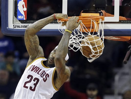 In this Jan. 21, 2015, file photo Cleveland Cavaliers' LeBron James dunks against the Utah Jazz during the second quarter of an NBA basketball game in Cleveland. Following a turmoil-filled start, LeBron James and his supporting cast are living up to extreme expectations and playing like championship contenders. (AP Photo/Mark Duncan)