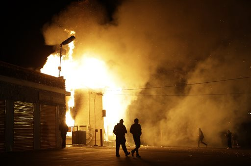 In this Monday Nov. 24, 2014 file photo, people walk away from a storage facility on fire after the grand jury decision was announced in Ferguson, Mo. More than 700 National Guard troops were stationed preemptively throughout the St. Louis region. But Missouri Gov. Jay Nixon was inundated with criticism for not deploying the Guard outside businesses along a prominent Ferguson road where looting and arson had occurred after Michael Brown's Aug. 9 shooting. (AP Photo/Jeff Roberson, File)
