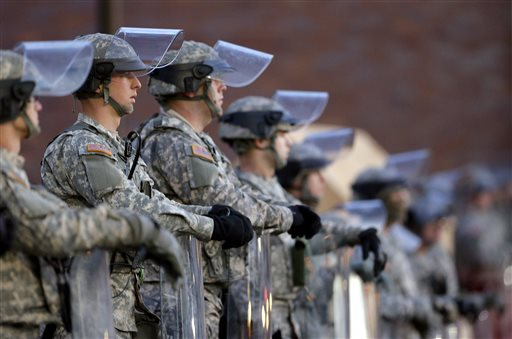 In this Nov. 25, 2014 file photo, National Guard troops stand in front of the Ferguson, Mo., Police Department a day after a grand jury's decision in the fatal shooting of Michael Brown. Newly released documents reveal that police planning for a grand jury announcement wanted Guard troops and armored Humvees stationed in the Ferguson neighborhood where Brown had been shot. But the records show the requests were not granted, because Missouri Gov. Jay Nixon preferred to use the Guard in a support role to police. (AP Photo/Charlie Riedel, File)