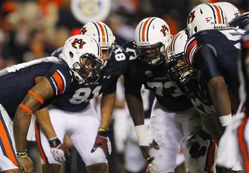 In this Nov. 30, 2013, file photo, Auburn quarterback Nick Marshall, left, calls a play in the huddle during the second half of an NCAA college football game against Alabama in Auburn, Ala. Auburn tied the score late in the fourth quarter when Nick Marshall flipped a pass to Sammie Coates over a defense that was drawn in by a run blocking offensive line. The NCAA rules committee has proposed changing the illegal man downfield penalty, shortening the distance lineman can move down field before the ball is thrown, which matches the NFL rule. (AP Photo/Butch Dill, File)