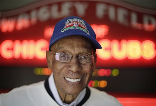 In this March 24, 2014 file photo, Chicago Cubs Hall of Fame slugger Ernie Banks smiles after an interview at the Cubs offices in Chicago. Banks died Jan. 23, 2015. Banks, who once said he wanted to have his ashes scattered at Wrigley Field, is at the center of a battle over his remains, with his estranged wife trying to prevent a longtime friend of Banks from having his remains cremated. (AP Photo/M. Spencer Green, File)