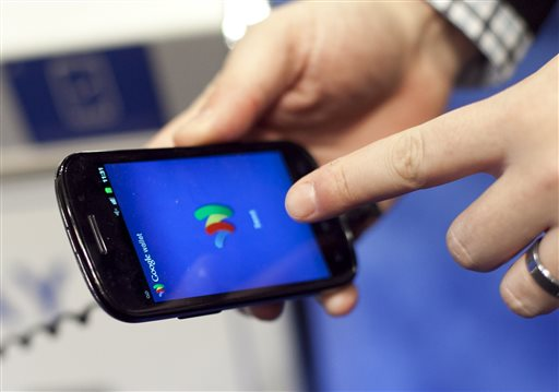 In this Jan. 17, 2012 file photo, a person tries a smartphone loaded with Google Wallet at the National Retail Federation in New York. Google is teaming up with three major U.S. wireless carriers in an effort to prod more people into using its mobile wallet and undercut the rapid success of Apple's rival payment service. (AP Photo/Mark Lennihan, File)