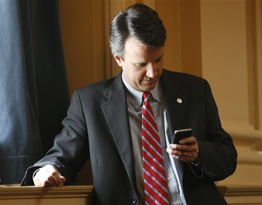 Del. Ben Cline, R-Rockbridge, checks his phone on the floor of the Virginia House of Delegates during the House session at the Capitol, Thursday, Feb. 26, 2015, in Richmond, Va. The General Assembly is expected to approve $400,000 in the state budget to compensate victims of involuntary sterilization by the state during the eugenics era. The surviving victims will be entitled to $25,000 each. (AP Photo/Steve Helber)