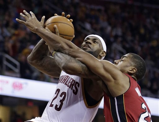 Cleveland Cavaliers' LeBron James, left, drives to the basket and is fouled by Miami Heat's Hassan Whiteside during the second quarter of an NBA basketball game Wednesday, Feb. 11, 2015, in Cleveland. (AP Photo/Tony Dejak)