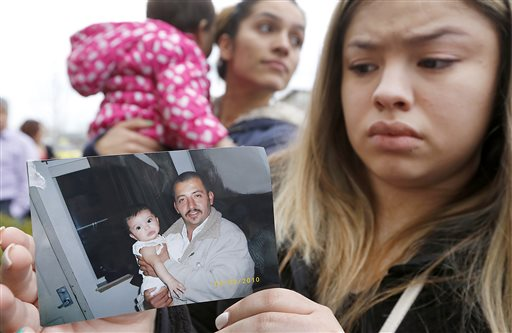 Erika Zambrano holds a 2010 photo of shooting victim Antonio Zambrano-Montes, Wednesday, Feb. 11, 2015, while standing outside the city hall building in Pasco, Wash. A rally was held in support of Zambrano-Montes, who was shot and killed by Pasco police officers during a confrontation at the busy intersection. (AP Photo/The Tri-City Herald, Bob Brawdy)