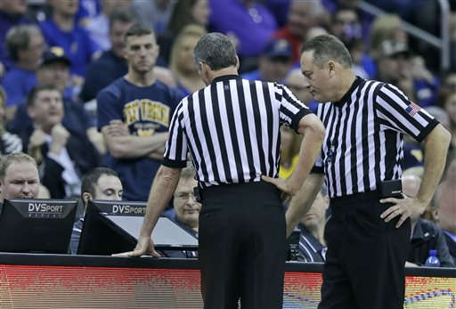 In this March 12, 2015, file photo, referees Mark Whitehead, right, and Terry Oglesby look at a replay during the second half of an NCAA college basketball game between West Virginia and Baylor in the quarterfinal round of the Big 12 Conference tournament in Kansas City, Mo. For the men's and women's basketball tournaments that begin this week, the NCAA for the first time will use a replay system that captures live high-definition video from multiple angles for immediate review. (AP Photo/Orlin Wagner, File)