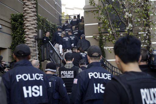 Federal agents enter an upscale apartment complex, Tuesday, March 3, 2015, in Irvine, Calif. Shortly after sunrise, federal agents swarmed the complex in the Orange County where authorities say a birth tourism business charged pregnant women $50,000 for lodging, food and transportation. The key draw for travelers is that the United States offers birthright citizenship. (AP Photo/Jae C. Hong)